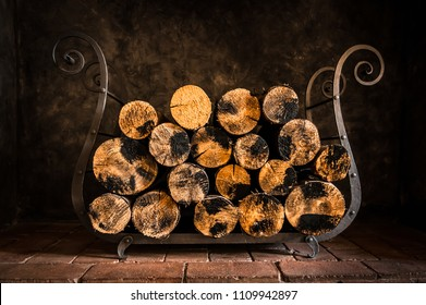 Firewood stack in dark at home for fireplace