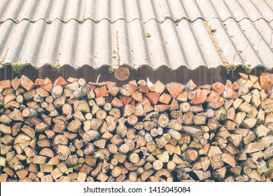 Firewood stacked wall under a canopy gable roof. Logs of firewood piled under the roof of slate. Fuel for stove heating. Country life. Wooden firewood stacked wall. Natural wood background.