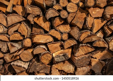 Firewood stacked in a woodpile. Firewood wall, closeup