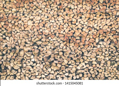 Firewood wall as a rustic background for design. Homemade firewood to air dry. A lot of firewood is stored in the end. Environmentally friendly fuel