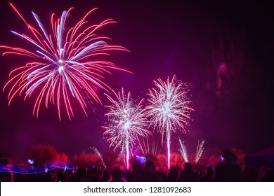 A firework display with three fireworks in view, two small ones and one big one.