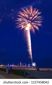 Firework from fun park at the beach Galveston Houston Texas USA in evening with last blue hour light