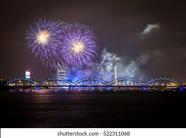 Firework in Riga over the river with bridge at night