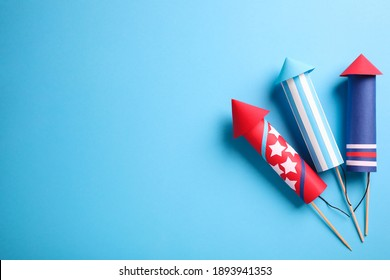 Firework rockets on light blue background, flat lay. Space for text