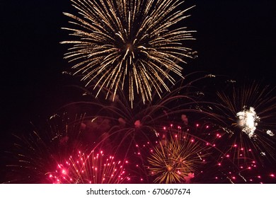 Firework in yellow, orange and red exploding in the night sky of a hot summer evening at a folk festival in bavaria