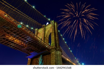 Fireworks bursting from the Brooklyn bridge at dusk with Independence day