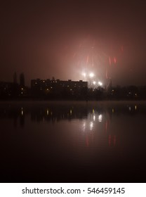 Fireworks in the city close to river, reflections on the water. New Year celebration.