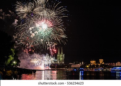Fireworks in Cologne/Germany at the River Rhine near the Cathedral. People are watching from the riverbank.