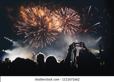 Fireworks and crowd of audience with hands raised at a summer music festival.