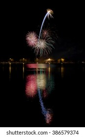 A fireworks display reflecting in water