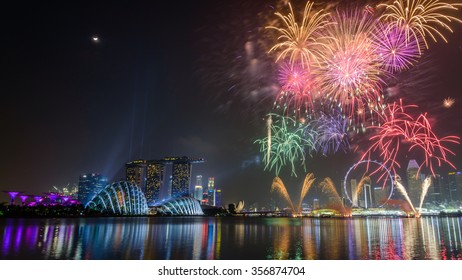 Fireworks displays along the Singapore River with Singapore Skylines, Downtown and Financial District buildings sparking reflection. Modern colorful City Background. Holiday urban night view.