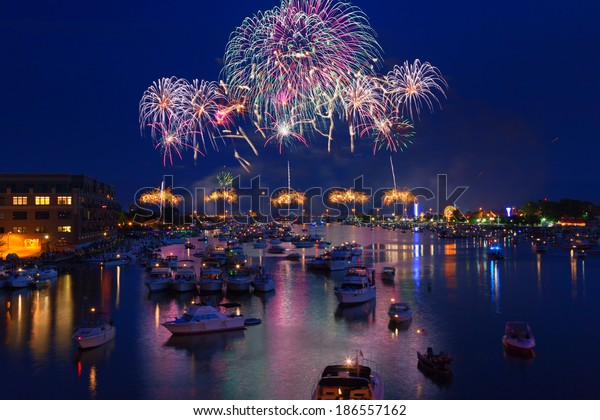 Fireworks explode in a glorious display over the Saginaw River at Bay City Michigan's annual fireworks show. Crowds gather in boats on the river to watch the display and celebrate Independence Day.