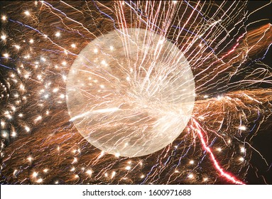 Fireworks exploding over a full moon, with glowing embers and light trails