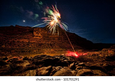 Fireworks exploding in a river canyon