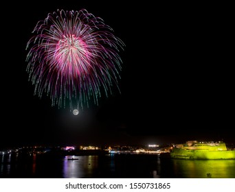 fireworks explosion in dark sky with city silhouette and colorful reflect on water