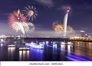 Fireworks firing up into the sky with a boat on a river below them, with a reflection on the water