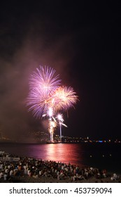 Fireworks illuminate the coastline of Nice at the 14th of july, bastille day.