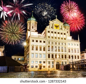 Fireworks at the illuminated town hall of Augsburg (Germany) at night.