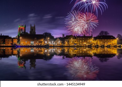 Fireworks at Kings Lynn in Norfolk UK 2018. Rockets exploding in a display over the Great River Ouse at night time. Historic town at night with reflections in the water