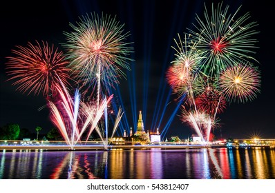 Fireworks lit up beautifully over dark sky and golden pagoda of temple close to the river with city light, blue beam laser and colorful reflection at night time to celebrate new year occasion