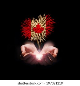 Fireworks in male hands in a heart shape with the Canada flag on a black background. Canada day. Welcome to Canada