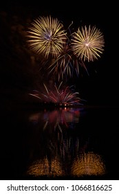 Fireworks of many colors on  display and refelcting in a lake