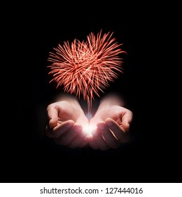 fireworks in the men's hands in the shape of a red heart on black background