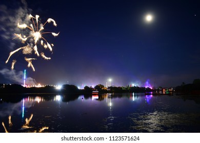 """Fireworks and a near full moon herald the end of the last day of the 2018 Isle of Wight Festival, as the headliner band """"The Killers"""" play on the main stage, seen in the distance in lights."""