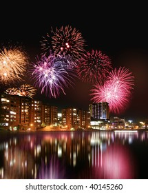 Fireworks in the night and colorful city night line reflecting from water