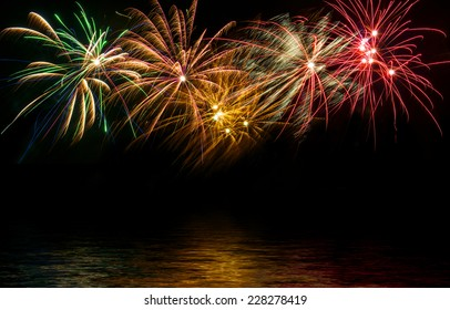 fireworks in the night sky reflected in water