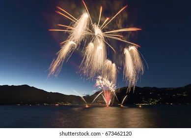Fireworks on the lakefront of Luino over the Maggiore Lake in a summer evening with blue sky and mountains in the background