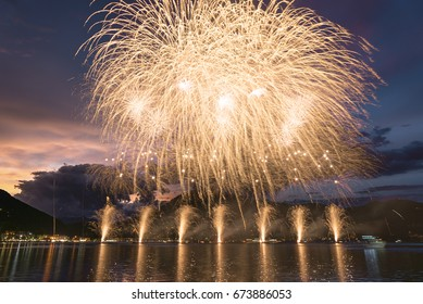 Fireworks on the Lugano Lake in a summer evening with cloudy sky at the sunset in the background