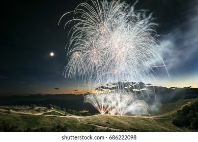 Fireworks on the top of the mountain Mottarone with twilight at the horizon and moon in summer season