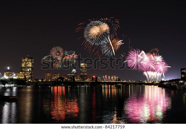 Fireworks over Boston on 4th of July celebration. Light reflections on Charles River, city skyline on background