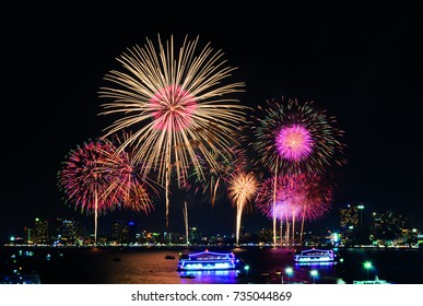 Fireworks over cityscape by the beach and sea surrounding with hotels, restaurant, and service boats and cruises for celebrating New Year eve and special occasion on holidays