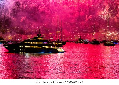 fireworks over yachts in cannes france, pink and red colours reflecting in the water, luxury holiday destination.