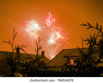 Fireworks in overcast sky over rooftops and hedges