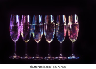 Fireworks reflected in the glasses of champagne. New Year's decoration.