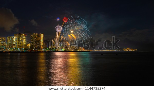 Fireworks seascape with moon and mars over waikiki skyline and diamond head crater landmark