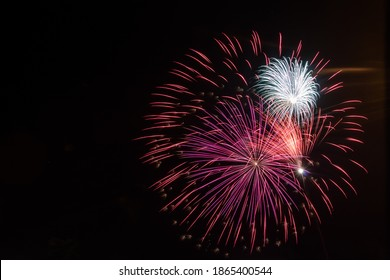 Fireworks in the sky of red, purple and white colors
