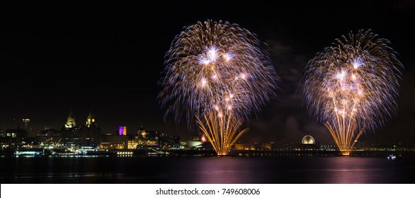 Fireworks take off from barges on the River Mersey during bonfire night in 2017 seen from the promenade on Seacombe, opposite the famous skyline of Liverpool.