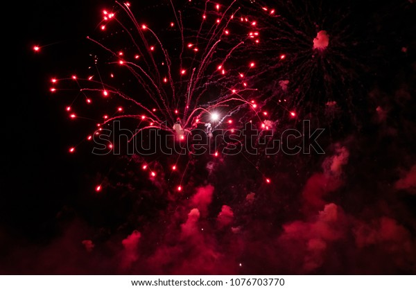 Fireworks with trails and smoke in red color against a black sky as background.