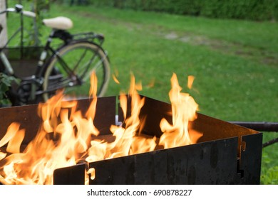 firing up the barbecue at a garden barbecue with a bike in the background