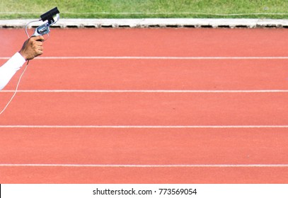firing a gun for starting race athletics with a white line track background