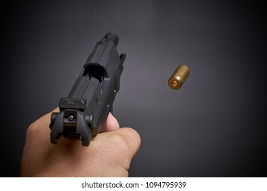 firing a handgun, flying empty shell