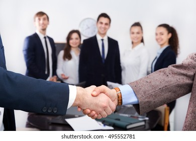 Firm handshake between two business partners at successful office meeting