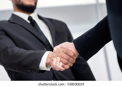 A firm handshake. Two successful smiling businessmen shaking hands with each other while discussing their of business doings. Young people talking in office