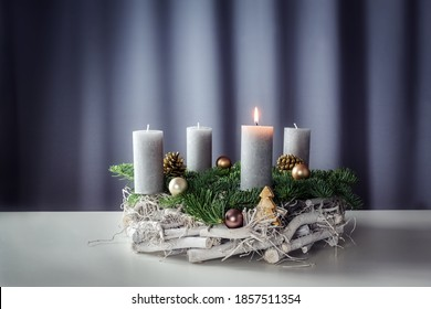 First advent with a burning candle on a wreath of white painted wood, fir branches and Christmas decoration against a purple-grey background, copy space, selected focus, narrow depth of field