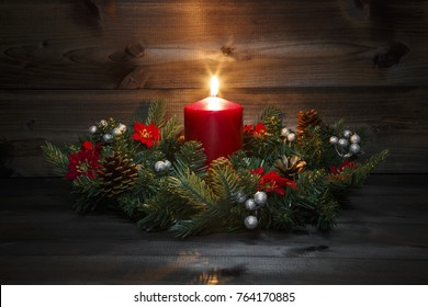 First Advent - Decorated Advent wreath with a red burning candle on a wooden background with festive atmosphere