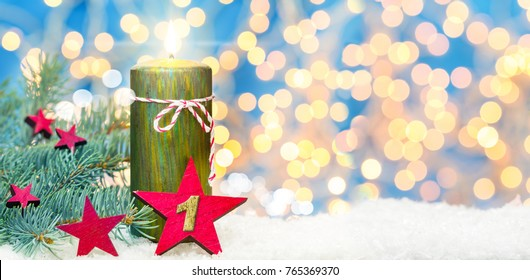First advent, advent decoration, candle and star in the snow before Bokeh